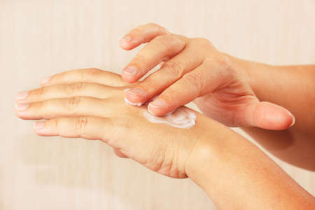 Female hands using skin cream close up photo
