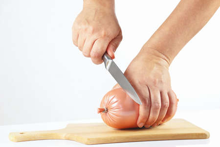 gastronome: Female hand with a knife sliced sausage on a white background