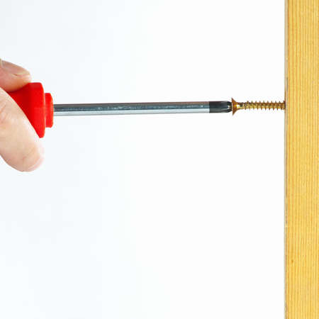fixate: Hand of the worker screws in a wooden wall with a screwdriver on a white background Stock Photo
