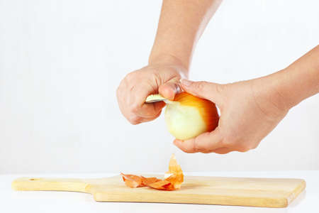 Womens hands peeling fresh onion with a knife on a white background