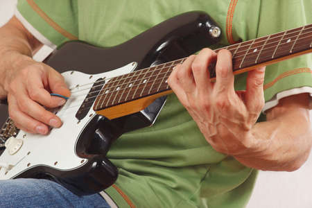 Guitarist put fingers for chords on electric guitar closeup photo