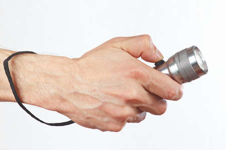 Hand holding a flashlight on a white background photo