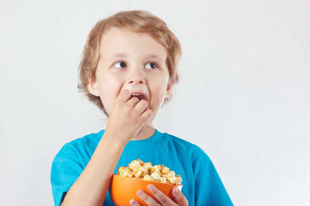 popcorn bowls: Little boy eating popcorn on a white