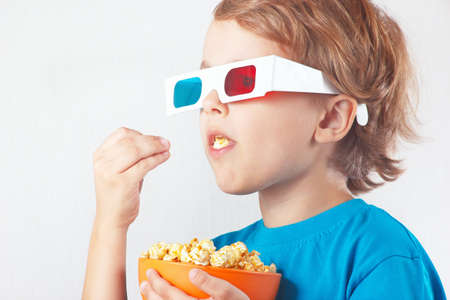 Young blonde boy in 3D glasses eating popcorn photo
