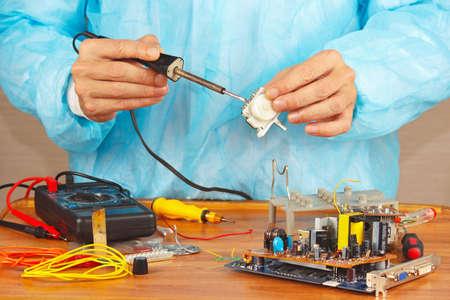 solder: Serviceman solder electronic hardware in the service workshop Stock Photo