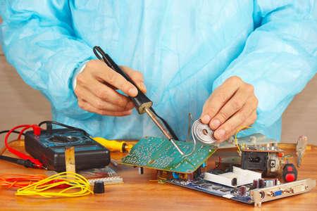 solder: Serviceman solder electronic board in the service workshop