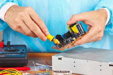 hardware repair: Master parses electronic hardware for repair in the service workshop