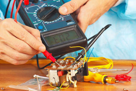 Serviceman checks electronic components of device with a multimeter