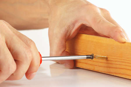 fixate: Hand of repairman screws in a wooden block with a screwdriver closeup