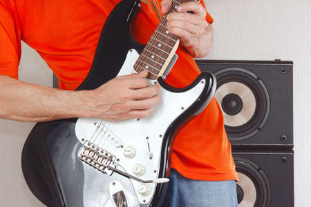 Hands of guitarist playing the electric guitar closeup photo