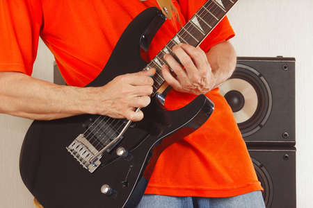 Hands of rock musician playing the electric guitar photo
