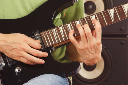 Hands of musician put guitar chords closeup photo