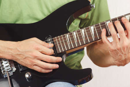 Guitarist playing the electric guitar closeup photo