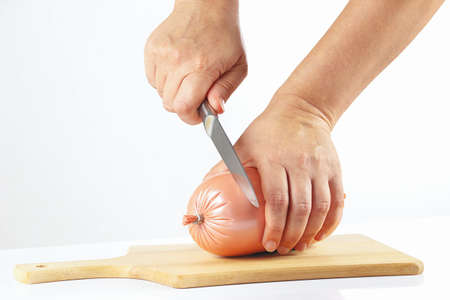 gastronome: Womens hand with a knife sliced sausage on a white background