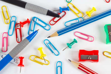 Pencil, pen, paperclips, sharpeners and pushpins on white desktop close up photo
