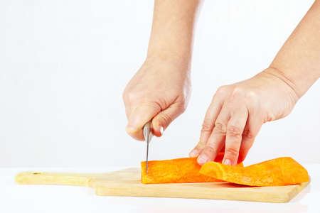 Female hands with a knife chops carrot on a cutting board close up photo