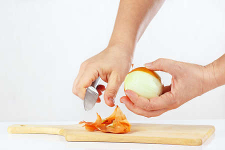 Female hands peeling raw onion with a knife on a cutting board closeup Reklamní fotografie
