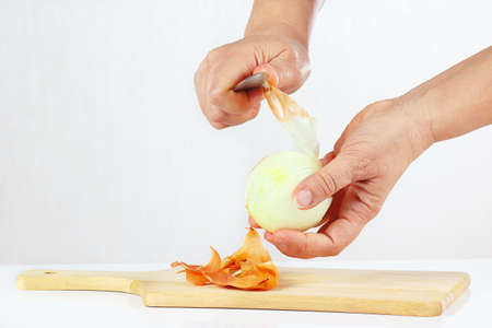 Hands peeling raw onion with a knife on a cutting board closeup