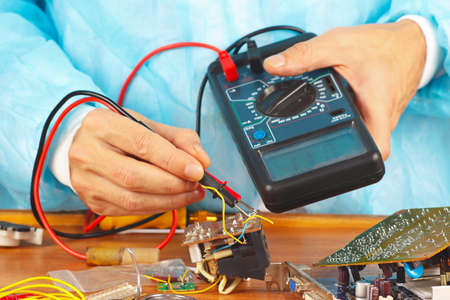 electrical engineering: Serviceman checks electronic hardware with a multimeter in the service workshop Stock Photo
