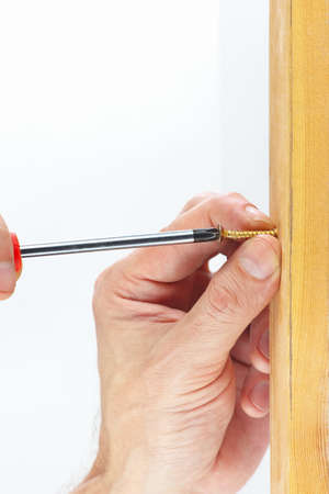 fixate: Hand of repairman screws in a wooden wall with screwdriver