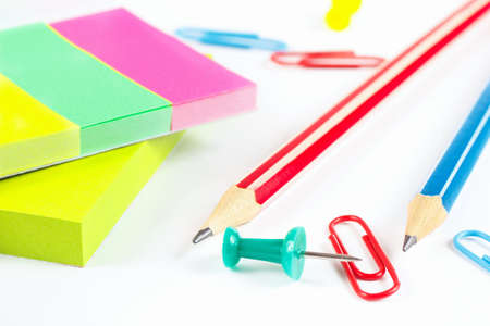Multicolored stationery on white desktop close up photo