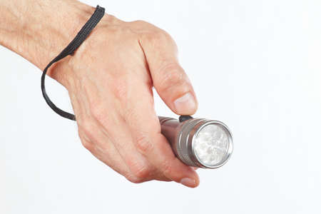 Hand holding a led torchlight on a white background photo