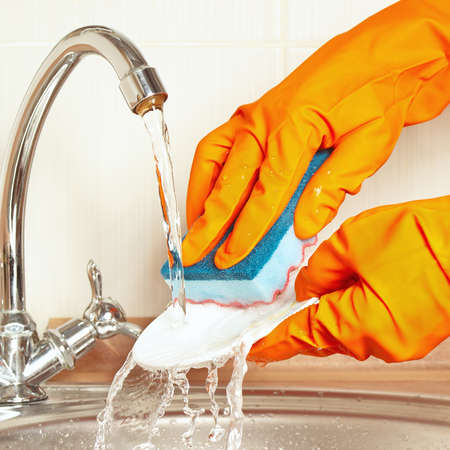 scour: Hands in rubber gloves with sponge wash the dirty dishes under running water