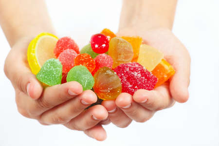 sweetmeat: Child hands with colorful sweetmeats and jelly closeup