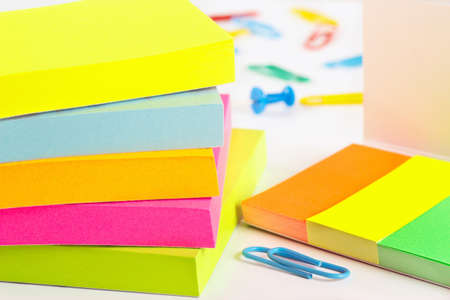 Paperclips, pushpins and multicolored stickers on white desktop close up photo