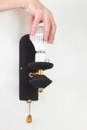electrolier: Hand unscrews led bulb in a lamp on a white wall Stock Photo