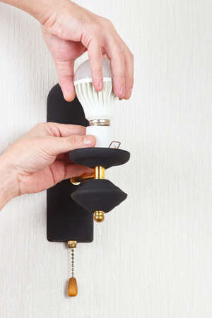 electrolier: Hand replace led bulb in the a lamp on a white wall