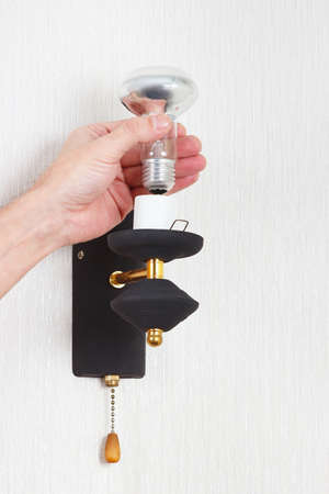 electrolier: Hand unscrews incandescent lightbulb in a lamp on a white wall Stock Photo