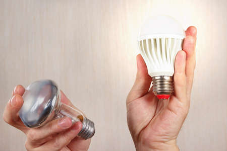 compared: Hands compared incandescent bulb and glowing ecofriendly led lamp on a light wood background