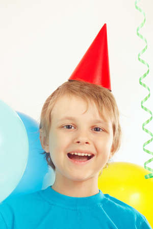 Little blonde boy in holiday cap with festive balls and a streamer Reklamní fotografie