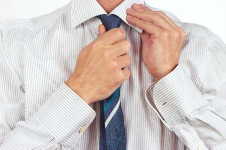 straighten: Man straighten his tie over bright shirt close up