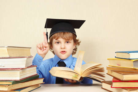 quoted: Little boy in academic hat quoted the old book Stock Photo