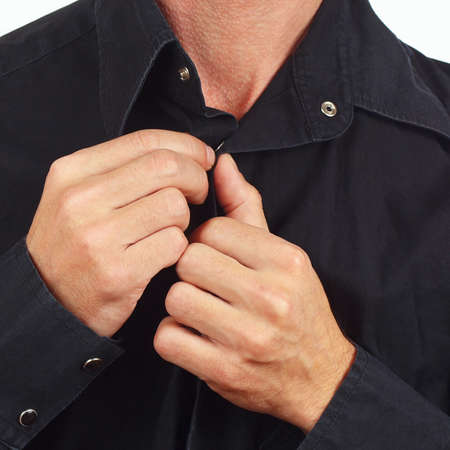 fastened: Hands a man fastened the buttons on the black shirt close up Stock Photo