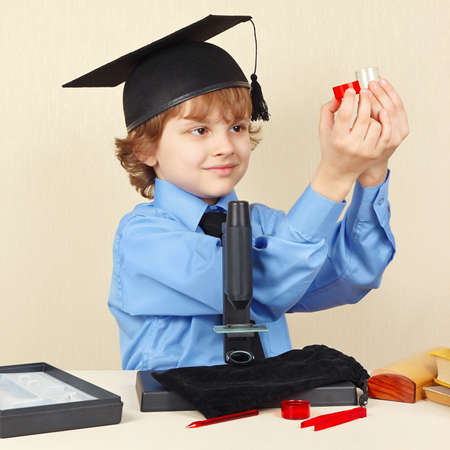 conducts: Little smiling boy in academic hat conducts scientific research with the microscope