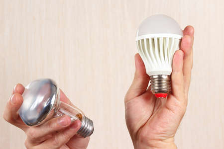 conventional: Hands compared incandescent bulb and ecofriendly led lamp on a light wood background