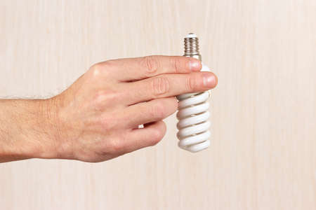 tungsten: Hand holding a tungsten bulb on a light wood background Stock Photo