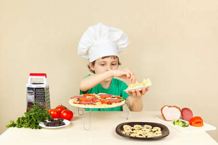 pizza crust: Little boy in chefs hat puts a grated cheese on the pizza crust Stock Photo
