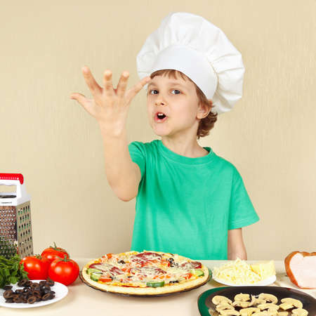 young boy: Little funny chef expressive enjoys a cooked pizza