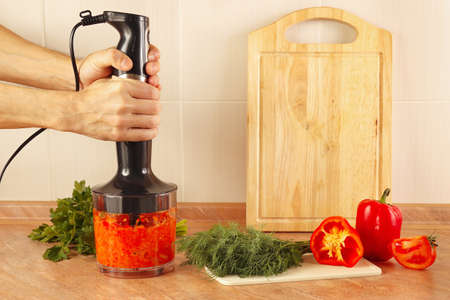 cook: Hands cooks mixed red pepper and tomato in a blender Stock Photo