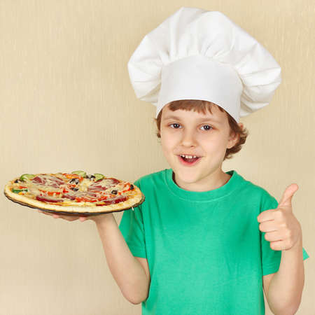 Little cute boy in chefs hat with a cooked appetizing pizza Reklamní fotografie
