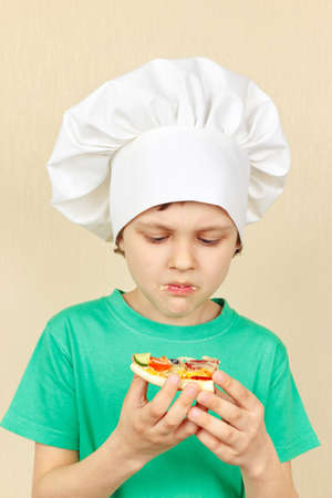 insipid: Little boy in chefs hat does not like the taste of cooked pizza