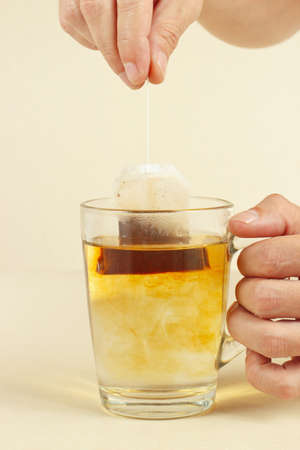 Hands brewed fresh tea in a glass with hot water