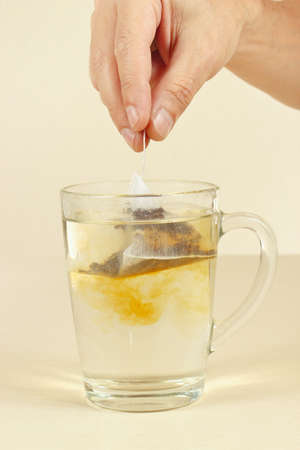 Hand puts the tea bag in a cup of water Imagens