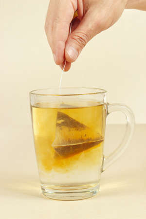 Hand brews tea bag in a cup of boiling water