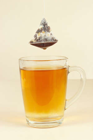 Tea bags over the glass with freshly brewed tea Imagens