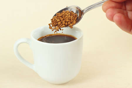 Hand pours granulated coffee from a spoon in a coffee cup